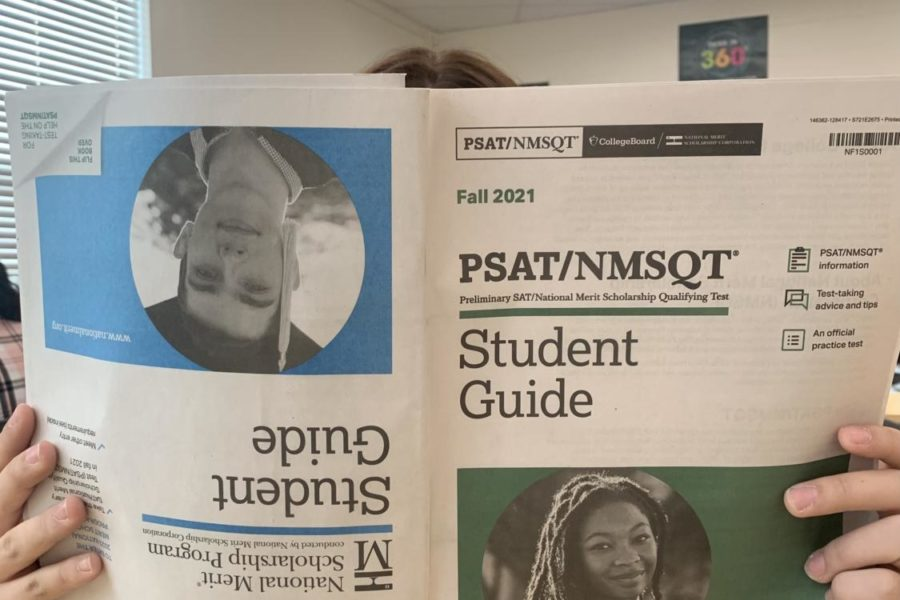 A student holds a copy of the PSAT preparation guide.